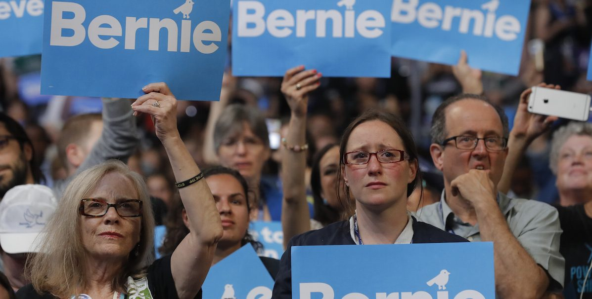 Supporters of former Democratic U.S. presidential candidate Senator Bernie Sanders listen as he speaks during the first session at the Democratic National Convention in Philadelphia, Pennsylvania, U.S., July 25, 2016. REUTERS/Jim Young - RTSJMPF