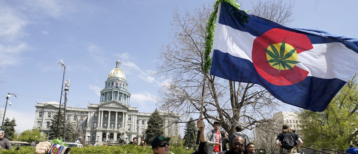 A man waves a Colorado flag with a marijuana leaf on it