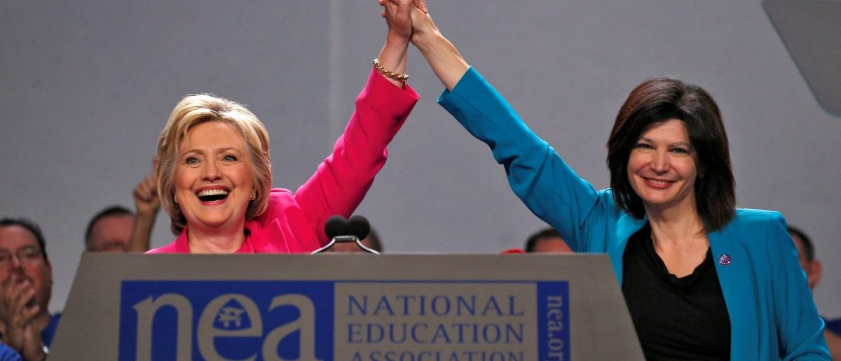 Hillary Clinton clasps hands with National Education Association's president Lily Eskelsen Garcia (REUTERS/Kevin Lamarque)