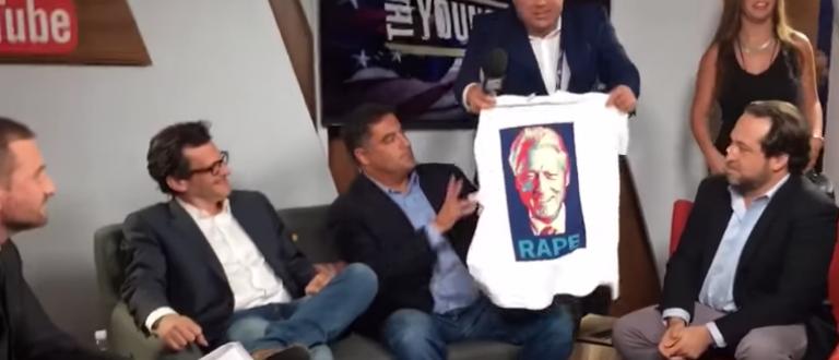 "Alex Jones presents Cenk Uygur with the ""Rape"" shirt (Infowars/YouTube Screenshot)"