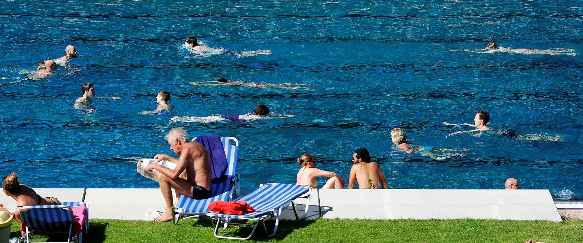 People relax at the public swimming pool of Schoenbrunner Bad on a sunny day in Vienna