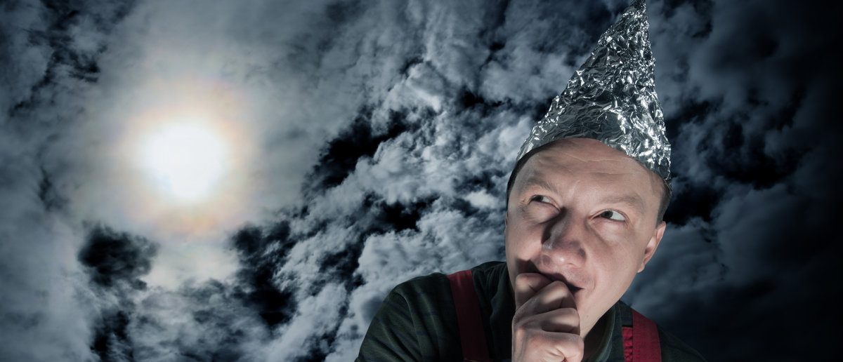 Scared suspecting man wearing a tin-foil hat against dark stormy sky (Shutterstock/Nomad_Soul)