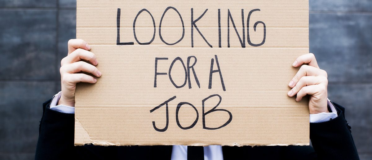 Young business woman holding sign Looking for a job. (Shutterstock/Luna Vandoorne)