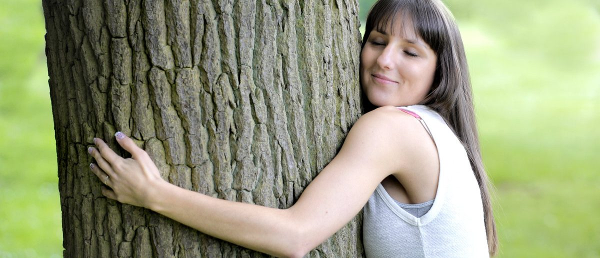 Young woman hugging a big tree. (Shutterstock/aldegonde)