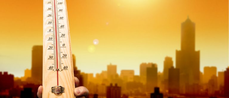 Heat wave in the city and hand showing thermometer for high temperature. (Shutterstock/Tom Wang)