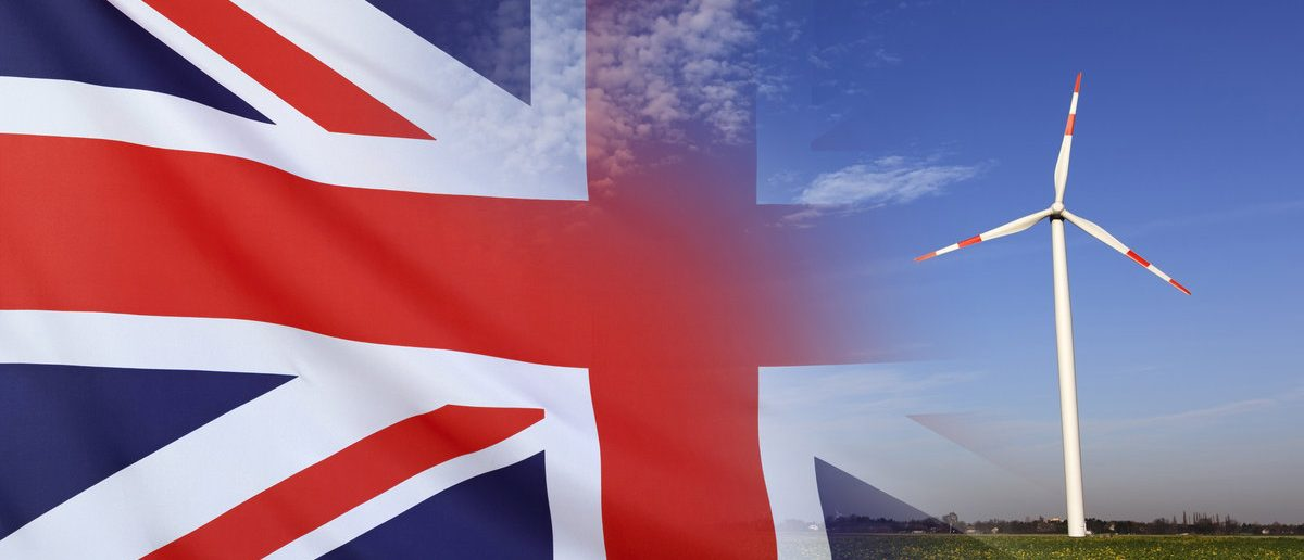Concept clean energy with flag of Great Britain fading away from wind turbine. (Shutterstock/Sehenswerk)