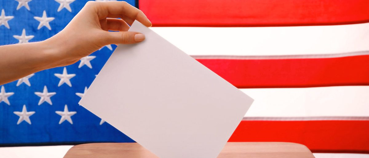 Hand putting down voting paper into a ballot box on American flag background (Shutterstock/Africa Studio)