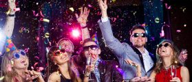 Cheerful people showered with confetti at a club party. [Shutterstock - YanLev]