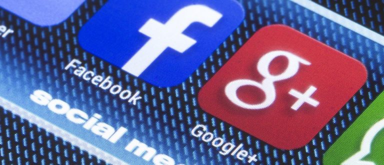 Popular social media icons Facebook, Google Plus and other on smart phone screen close up. [Shutterstock - quka]