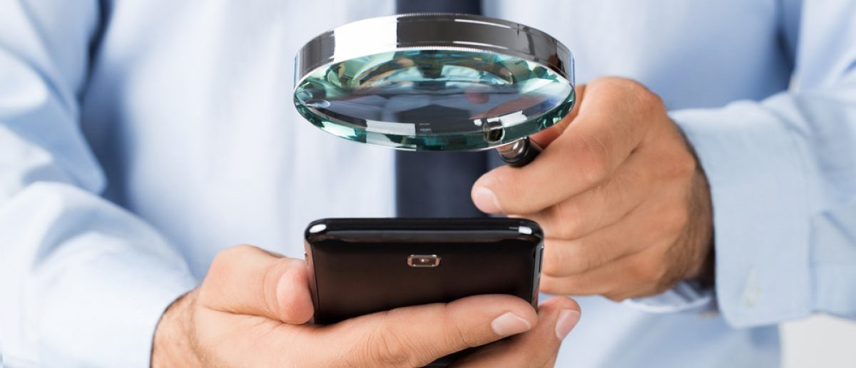 Close up of young businessman searching, spying the mobile, smart phone. [Shutterstock - rangizzz]