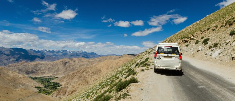 August 9, 2014. Car running pass the road on high altitude Ladakh-Leh road in Himalayan mountain, state of Jammu and Kashmir, India. Photo: Shutterstock
