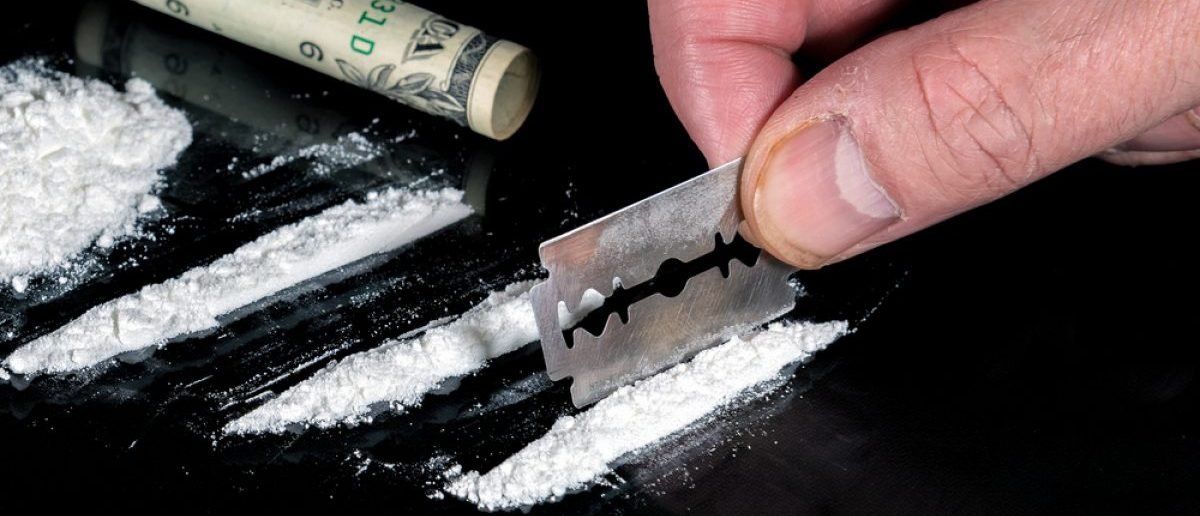 A hand holds a steel razor blade as it cuts a line of cocaine. Rolled bill is at the top. [Shutterstock - Doug McLean]