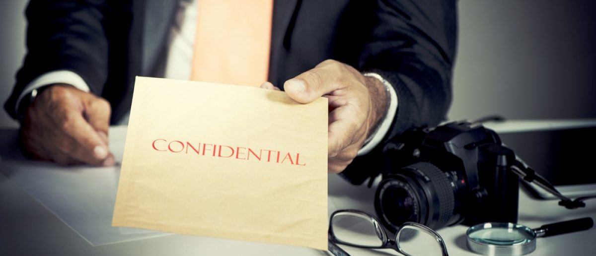Detective giving a confidential envelope. [Shutterstock - weRpix]
