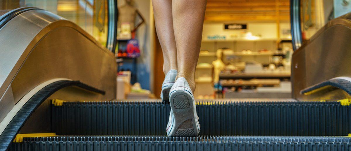 Woman on escalator/ Shutterstock