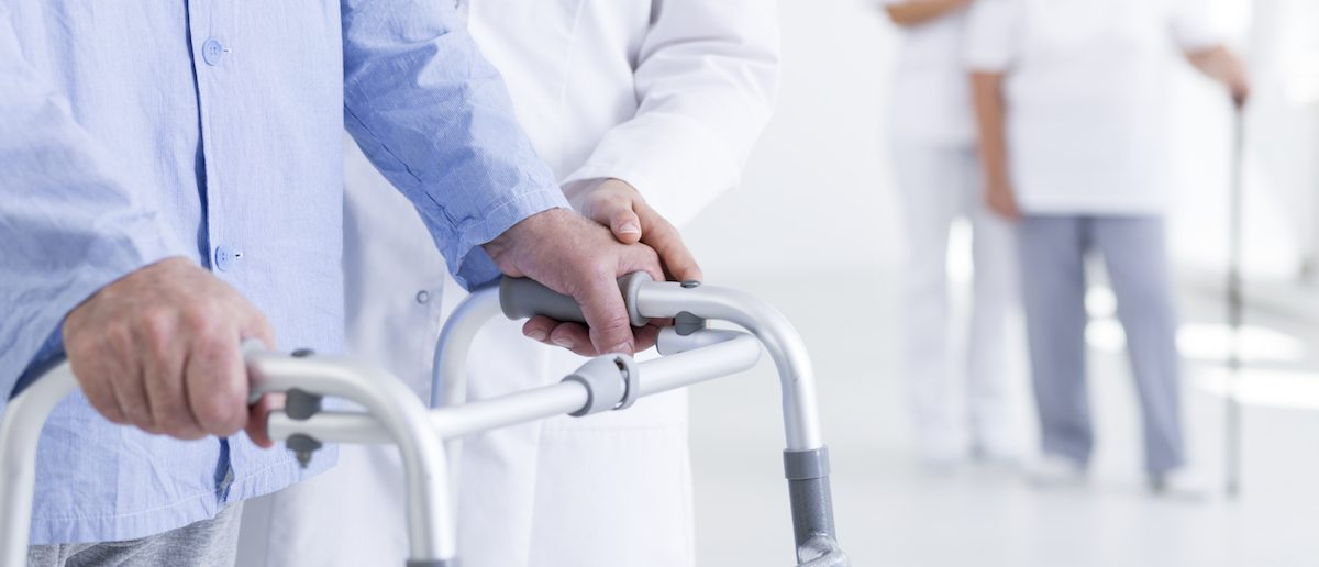 Closeup shot of a senior walking with walker assisted by a nurse. (Shutterstock/Photographee.eu)