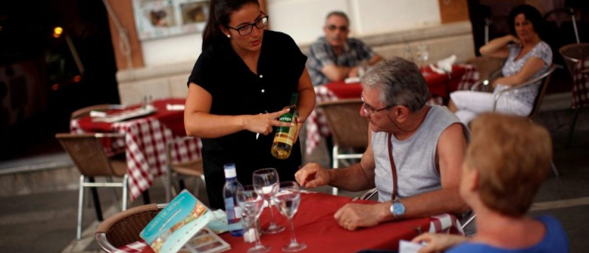 "A waitress serves wine to customers at the terrace of the ""Casino de Ronda"" restaurant in downtown Ronda restaurant in downtown Ronda, near Malaga, southern Spain July 24, 2014. REUTERS/Jon Nazca"