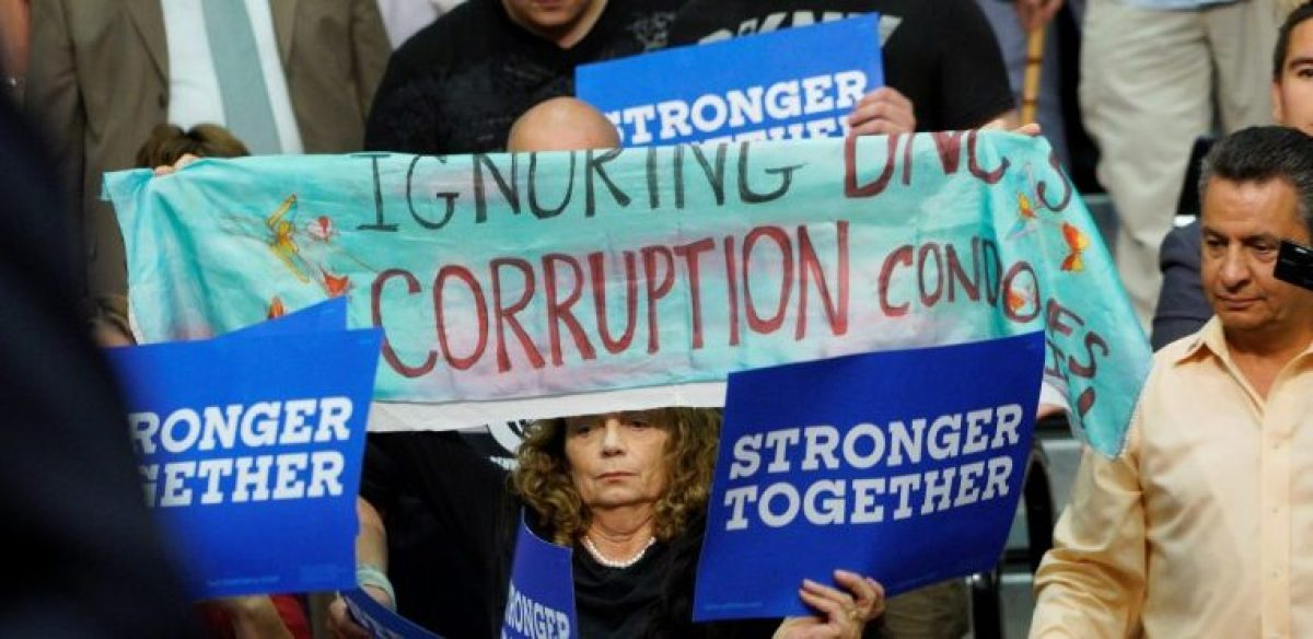 A protestor holds up a sign referring to DNC corruption at a rally for U.S. Democratic presidential nominee Hillary Clinton in Commerce City, Colorado, U.S., August 3, 2016. REUTERS/Rick Wilking
