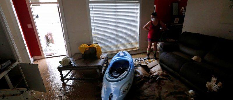 Johnette Folse stands in her flood damaged living room in Denham Springs