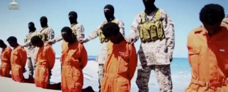 Islamic State militants stand behind what are said to be Ethiopian Christians along a beach in Wilayat Barqa, in this still image from an undated video made available on a social media website on April 19, 2015. REUTERS/Social Media Website via Reuters TV/File Photo
