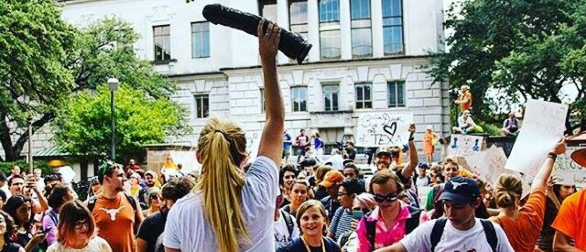 Campus activist Rosie Zander rouses a crowd with a girthy dong. From Zander's Facebook profile.