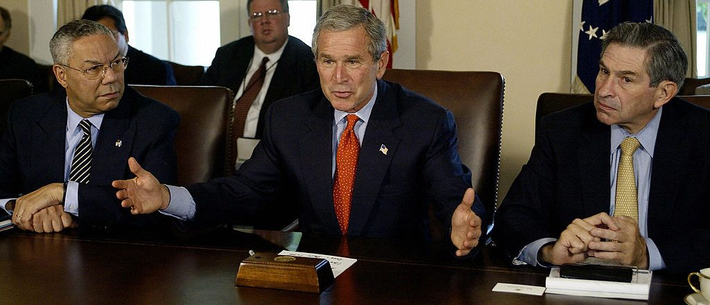 US President George W. Bush(C) delivers a few words to the media on the growth of the economy before a Cabinet meeting 07 October, 2003 at the White House in Washington, DC. US Secretary of State Colin Powell(L) and Deputy Secretary of Defense Paul Wolfowitz(R) look on. PAUL J.RICHARDS/AFP/Getty Images