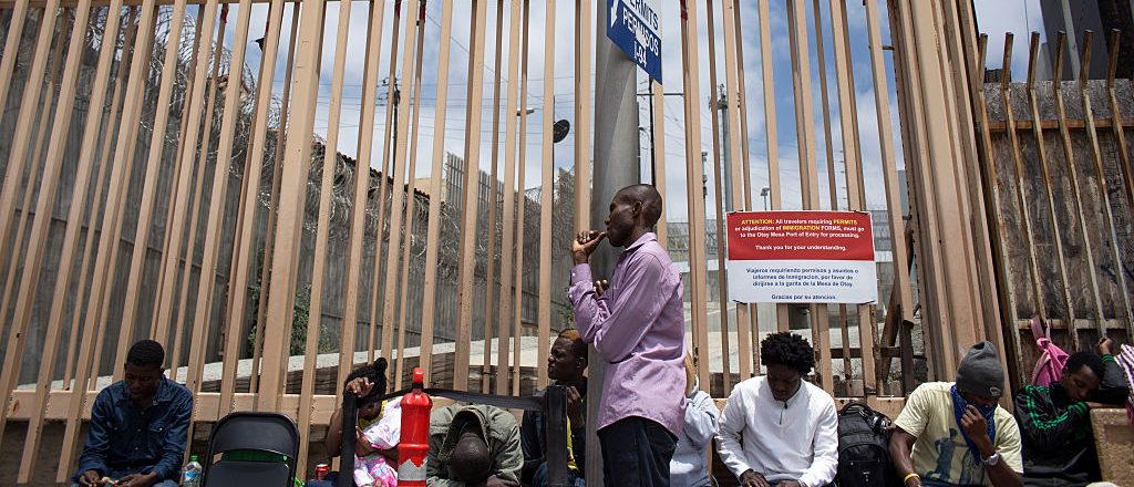 Jonas Despinasse (C), from Haiti, stands as he waits with other migrants for the Custom and Border Protection agents to seek for asylum in the United States, on the Mexican side of the San Isidro Port of Entry on May 26, 2016, in Tijuana, northwestern Mexico. On the past couple of weeks some 600 hundred migrants, mainly from Haiti and some African countries, arrived to Tijuana to try to ask for asylum to the U.S. government through the local points of entry. / AFP / GUILLERMO ARIAS (Photo credit should read GUILLERMO ARIAS/AFP/Getty Images)