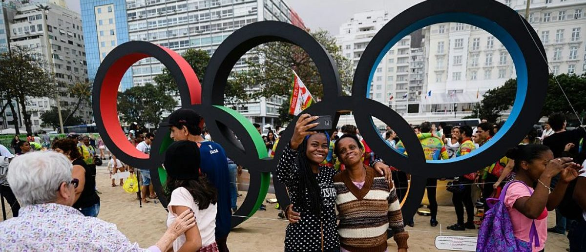 Olympic fans take photographs and pose for selfies in front of the Olympic rings on Copacabana beach in Rio de Janeiro, on 30 July 2016. The city is making last minute preparations for the events and celebrations as the 2016 Rio Olympic Games are set to begin in Rio on August 5 and run until August 21, 2016. LEON NEAL/AFP/Getty Images
