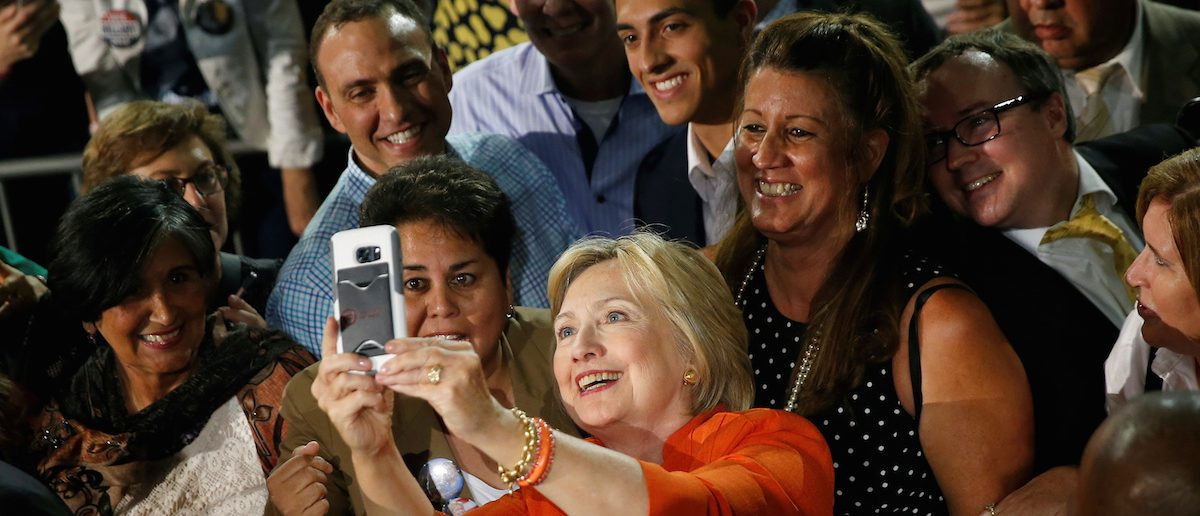 Democratic presidential nominee Hillary Clinton takes a selfie with supporters during a campaign rally in Kissimmee, Florida, August 8, 2016. (REUTERS/Chris Keane)