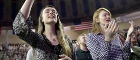 Lesley Chambers (L) of Champaign, Illinois and Brensley Baker of San Francisco, California, hold their hands up as they sing before Republican presidential candidate Donald Trump arrival at Liberty University in Lynchburg, Virginia, January 18, 2016