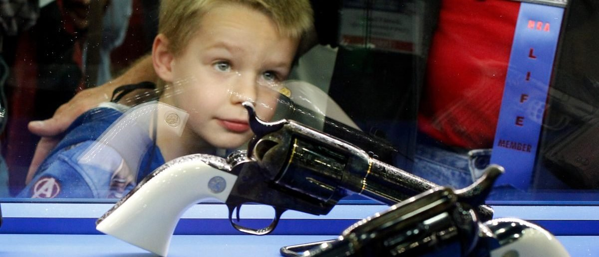 Asher Thomson (5) looks over a pair of Colt revolvers at the National Rifle Association's (NRA) annual meetings and exhibits show in Louisville, Kentucky, May 21, 2016