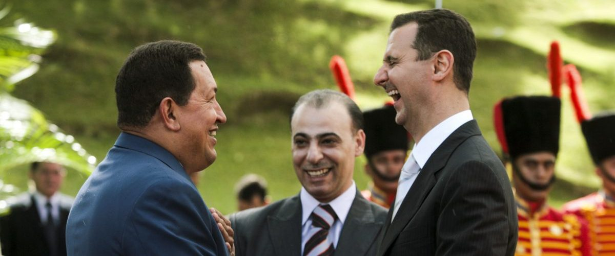 Syria's President Bashar al-Assad (R) shares a laugh with his Venezuelan counterpart Hugo Chavez (L), while they shake hands at Miraflores Palace in Caracas June 26, 2010. Picture taken June 26. REUTERS/Miraflores