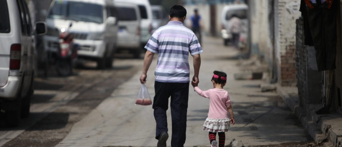 """A migrant worker holds his daughter's hand as they leave a market in a residential area for migrant workers in Beijing May 27, 2011. The education of the children of migrant workers, who number 240 million in China, is one of the top concerns of the Chinese State Council, Premier Wen Jiabao said during an online chat with Internet users in February. The council also said that preschools are currently the """"weakest"""" part of the education system. Picture taken on May 27, 2011. REUTERS/Jason Lee"""