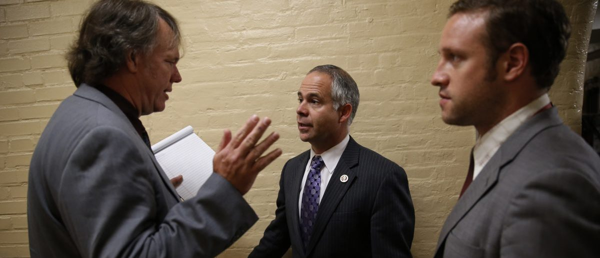 Rep. Tim Huelskamp (R-KS) (C) listens to questions from reporters about House Majority Leader Eric Cantor's Republican primary election defeat in a hallway of the U.S. Capitol building in Washington June 11, 2014. REUTERS/Jim Bourg (UNITED STATES - Tags: POLITICS) - RTR3TAB5