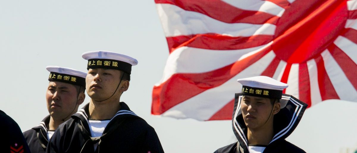 Soldiers of Japan's Maritime Self Defense Force stand in front of the country's naval ensign during the handing-over ceremony of the Izumo warship at the Japan United Marine shipyard in Yokohama, south of Tokyo March 25, 2015. Japan's Maritime Self Defense Force on Wednesday took delivery of the biggest Japanese warship since World War Two, the Izumo, a helicopter carrier as big as the Imperial Navy aircraft carriers that battled the United States in the Pacific.  REUTERS/Thomas Peter
