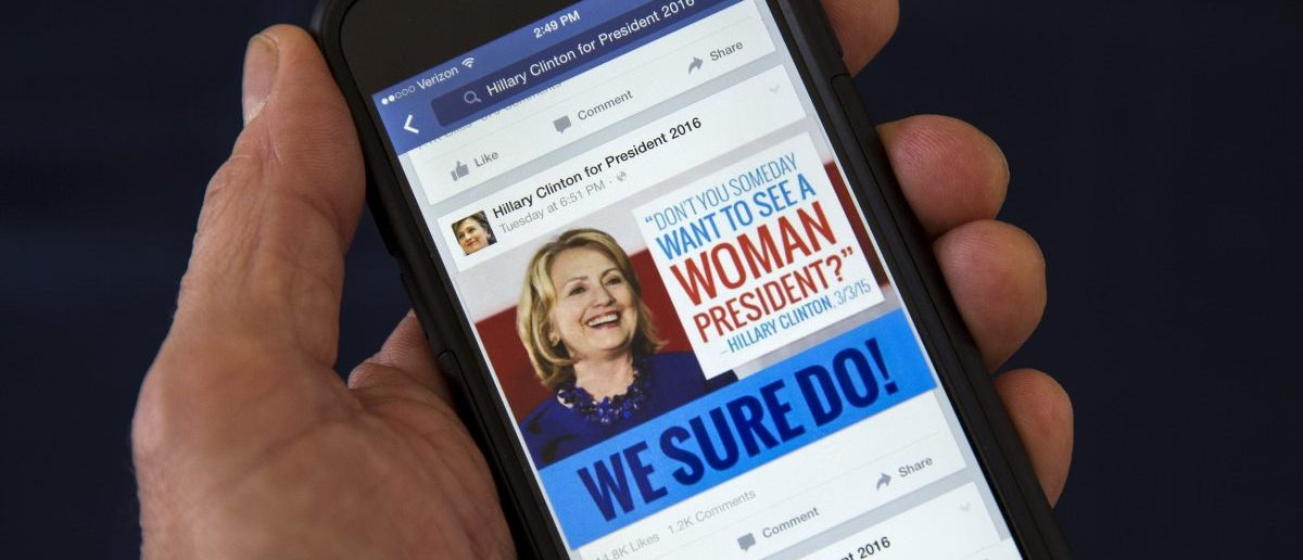 A mobile phone shows a Facebook page promoting Hillary Clinton for president in 2016, in this photo illustration taken April 13, 2015. By one estimate U.S. online political advertising could quadruple to nearly $1 billion in the 2016 election, creating huge opportunities for digital strategy firms eager to capitalize on a shift from traditional mediums like television. REUTERS/Mike Segar - RTR4X894