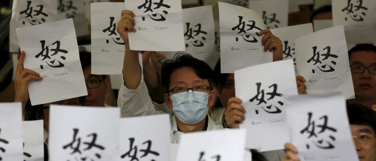 "Doctors hold placards reading the Chinese character for ""Anger"" REUTERS/Bobby Yip"