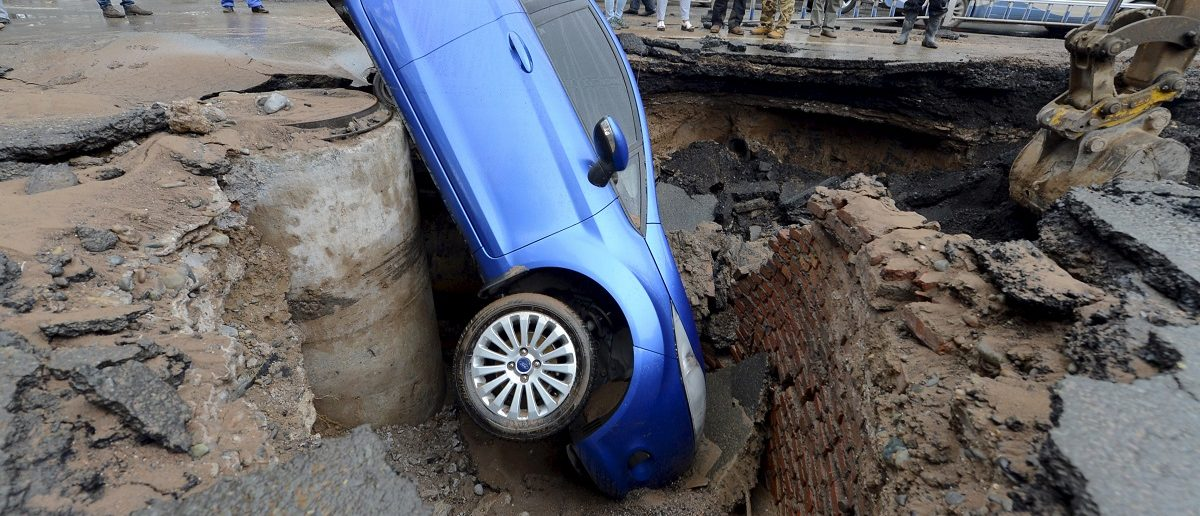 Workers look on as a car is stranded in a sinkhole on a street in Lanzhou, Gansu province, China, September 9, 2015. The driver managed to get out of the car unharmed and no one was injured during the incident, local media reported. REUTERS/Stringer