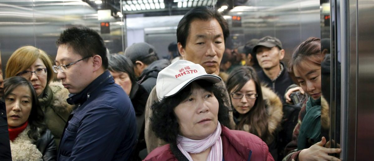 Family members of passengers onboard Malaysia Airlines flight MH370 which went missing in 2014, ride an elevator in the Beijing office of Malaysia Airlines as they leave the office after their gathering on the second anniversary of the disappearance of MH370, in Beijing, China, March 8, 2016. REUTERS/Kim Kyung-hoon