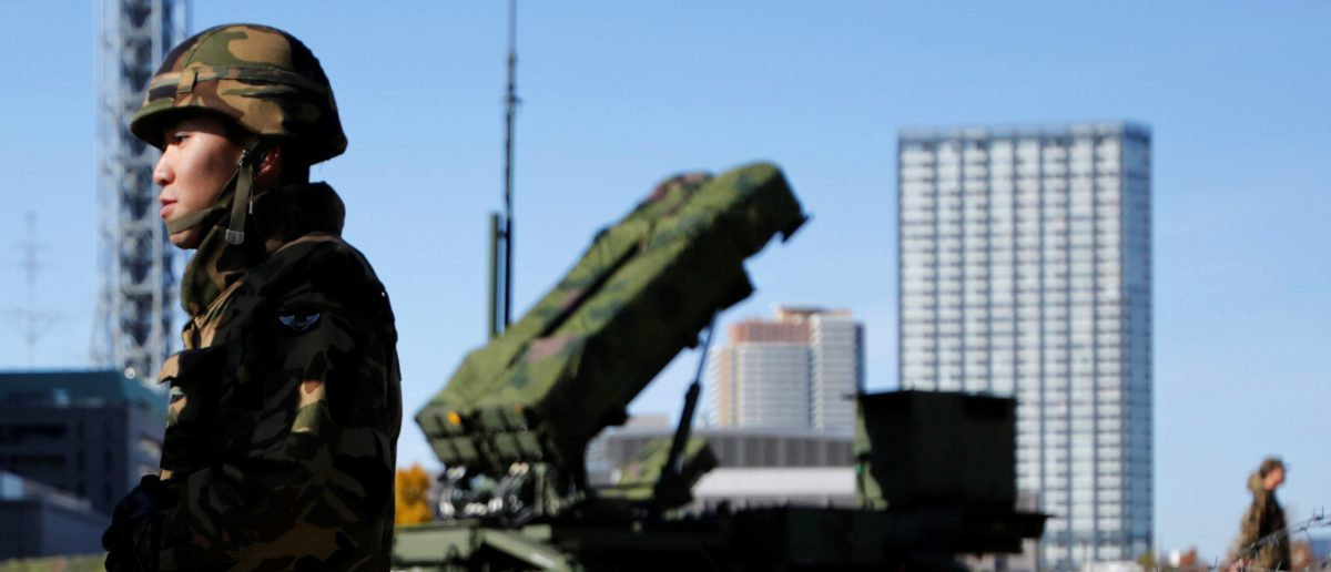 Members of the Japan Self-Defence Forces stand guard near Patriot Advanced Capability-3 (PAC-3) land-to-air missiles, deployed at the Defense Ministry in Tokyo December 7, 2012.  REUTERS/Issei Kato/File Photo