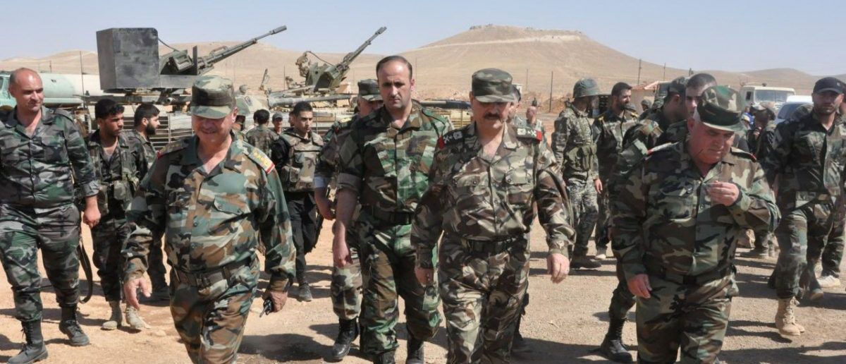 Syrian Minister of Defense, Fahd Jassem al-Freij(C), walks during a visit to Syrian regime soldiers in Aleppo, Syria in this handout picture provided by SANA on August 9, 2016. Picture taken August 9, 2016. SANA/Handout via REUTERS