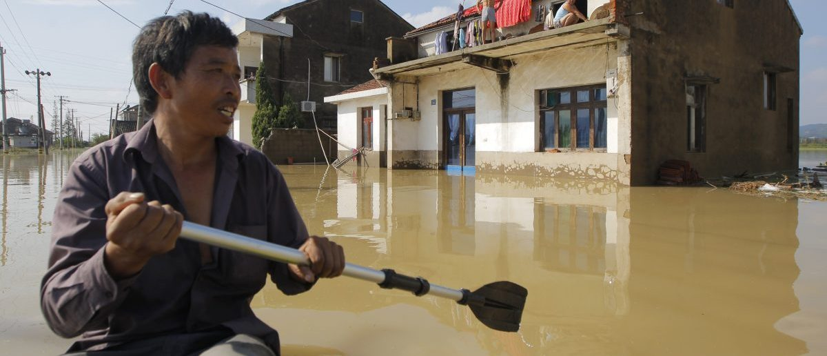 A man paddles a raft amidst a flooded street as residents are seen atop a partially submerged building in Yuyao, Zhejiang province October 10, 2013. Power remains cut on Thursday for the third consecutive day for tens of thousands of households in Yuyao, Zhejiang Province, after Typhoon Fitow-triggered downpours lashed the city. Floodwater retreated slowly but waist-deep water remained on Thursday in many parts of the worst-hit city, where 70 percent of the downtown area was submerged, Xinhua News Agency reported. Picture taken October 10, 2013. REUTERS/China Daily