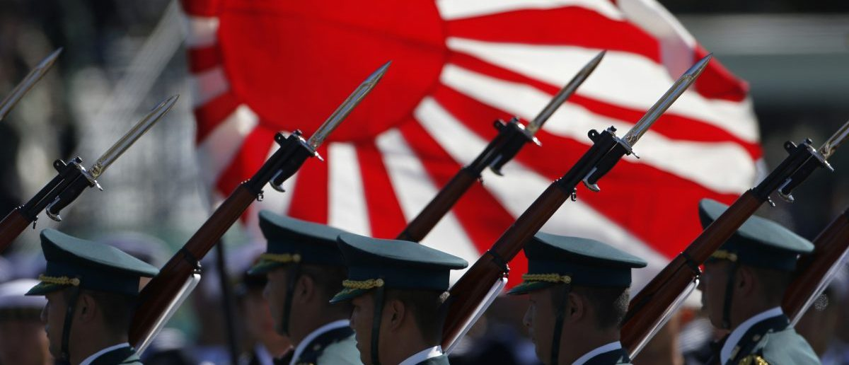 Japan Self-Defence Forces' (SDF) troops march during the annual SDF troop review ceremony at Asaka Base in Asaka, near Tokyo October 27, 2013. Japanese Prime Minister Shinzo Abe, in an interview published on Saturday, said Japan was ready to be more assertive towards China as Beijing threatened to strike back if provoked. REUTERS/Issei Kato