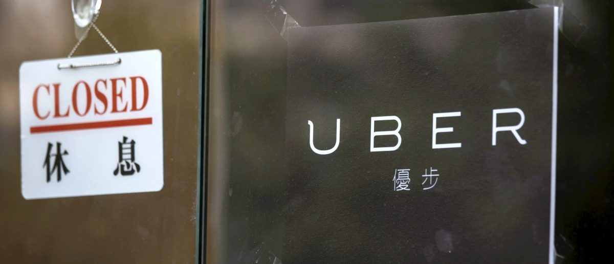 """A closed sign is seen at the office of taxi-hailing service Uber Inc in Hong Kong, China August 12, 2015. Police raided the Hong Kong offices of taxi-hailing service Uber Inc on Tuesday and arrested five drivers for the """"illegal use of vehicles for hire"""", police said. REUTERS/Tyrone Siu"""