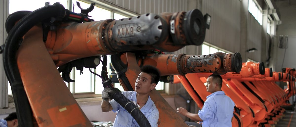 Workers fix second-hand robots in a factory in Shanghai, August 21, 2015. Picture taken August 21, 2015. REUTERS/Aly Song