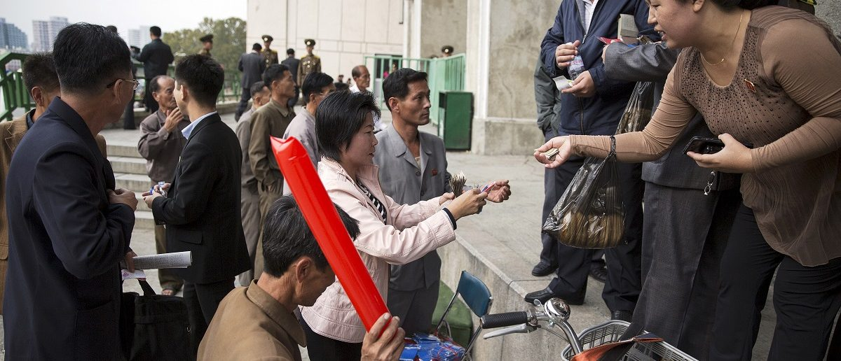 People use North Korean won and U.S. dollars to buy inflatable clappers at a black market exchange rate before a football match at the Kim Il Sung Stadium in Pyongyang October 8, 2015. Picture taken October 8, 2015. To match Insight NORTHKOREA-CHANGE/ REUTERS/Damir Sagolj