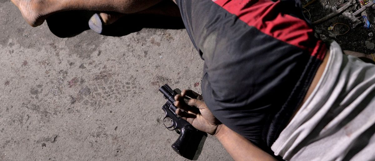 """The body of a man is pictured with a gun under his hand, whom police said was killed during a drug bust operation on """"Shabu"""" (Meth), in Manila, Philippines, August 18, 2016. REUTERS/Ezra Acayan/File Photo"""