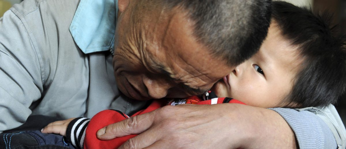 Wang Bangyin, a local farmer, holds his rescued son after the pair were reunited at Guiyang Welfare Centre for Children in Guiyang, Guizhou province October 29, 2009. Wang's son was among 60 children seeking parents after police freed them from human traffickers. The Ministry of Public Security released photos of the children on Tuesday, Wang and his son were the first from the list to be reunited, China Daily reported. Picture taken October 29, 2009. REUTERS/China Daily