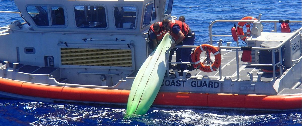 A United States Coast Guard patrol boat crew lifts a kayak found among debris near Sanibel, Florida during a search for a family that went missing on their sailboat