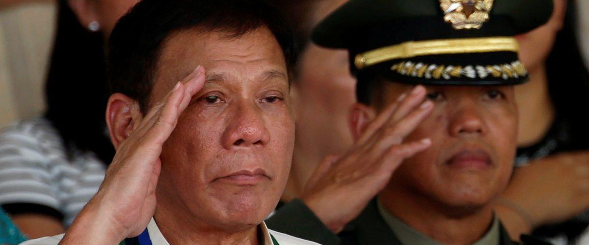 Philippines President Rodrigo Duterte salutes next to a military officer at main military Camp Aguinaldo in Quezon city Metro Manila