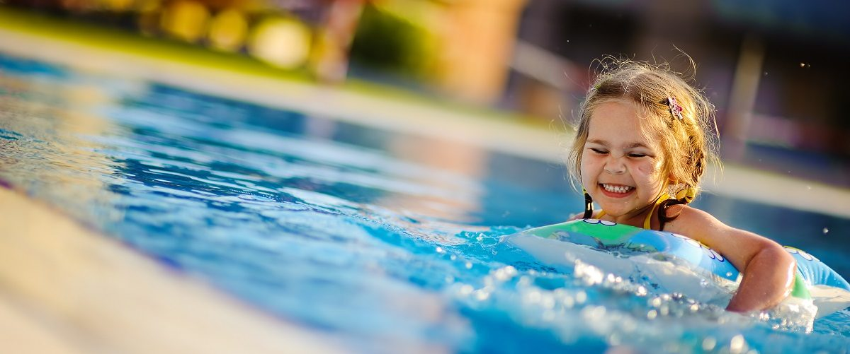 Girl playing with an inflatable at a pool. Natalia Kirichenko/Shutterstock.